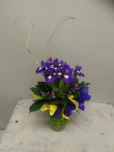 """Week three:  Vase bouquet. Iris bouquet (10), umbrella palm foliage, misty statice, tortured willow feature, purple cello and yellow non woven """"scrunches""""."""