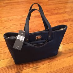 🌻Tommy Hilfiger nylon blue bag🌻 Snap closure. Clutch handle. Slot front pocket with separate zipper storage. Inside there is a zippered storage pocket and a slot storage pocket. Measurements are 12 inches across the bottom, 4 inches bottom side, 10 inches high. Handle measures 14 inches. Tommy Hilfiger Bags Totes
