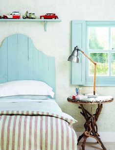 Bright bedroom with a matching light blue headboard and window, rustic striped linens and a display of vintage toy cars