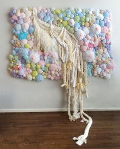 Jaz Harold -art wall hanging in pastel colored fluff balls and pompoms and breasts and braids