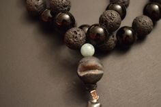 Hematite wire wrapped cross paired with lava stone and onyx. A couple small amazinite are used as well.