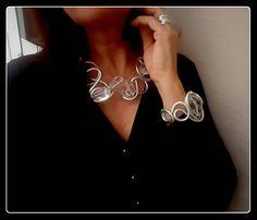 Collana realizzata in filo di alluminio argentato, modellato a mano, con 5 bellissime pietre di Cristallo di Rocca, di grande formato.    Il CRISTALLO DI ROCCA, nella Cristalloterapia, amplifica l'energia e stimola il sistema immunitario.  Inserito in questa collana, la sua trasparenza in contr