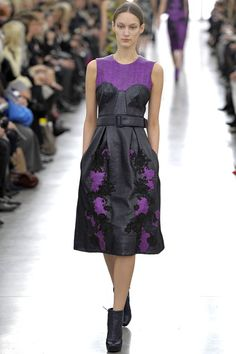 Erdem AW 13 Catwalk.  Erdem's sleeveless design is shaded in one of the season's key colors; magenta. The rich hue is woven with black fibers in a mirrored floral print placed on the box-pleated skirt. Patent textured leather appears as a paneled bodice and belt, adding a dark, tough edge to the piece.