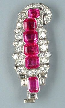 An Art Deco ruby and diamond brooch, by Cartier, circa 1930. The stylised Persian palm set with a central line of rectangular step-cut rubies, to a border of circular and baguette-cut diamonds, signed Cartier London, length 4.0cm. #ArtDeco #Cartier #brooch