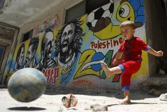 A Palestinian boy kicks a ball in front of graffiti wall murals depicting (L to R) Portugal's Cristiano Ronaldo, Argentina's Lionel Messi, Netherlands' Arjen Robben and Italy's Andrea Pirlo on June 23, 2014 at the Khan Yunis refugee camp in the southern Gaza Strip. (Photo: Said Khatib/AFP/Getty Images)