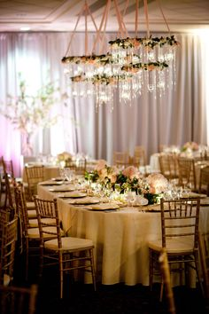Add an elegant touch by hanging chandeliers dripping in flowers, candles, and crystals above your tables.