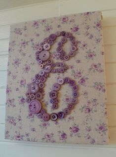 fabric-covered canvas with button letter