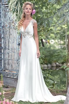 Style Austin  Chic sophistication is found in this elegant Palatzo satin sheath wedding dress with a Swarovski crystal embellishment at the waist, and Swarovski crystal cap-sleeves, trailing into a dramatic illusion back, edged in glittering crystals. Finished with crystal button over zipper closure.