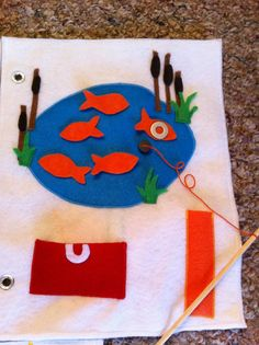 My Quiet Book: Felt Busy Book fish have washers to get caught by magnet on fishing rod. Love the cattails also!