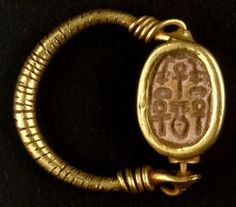 A scarab set in a golden ring with a relief gold-wire decoration near the bezel. Symmetrical hieroglyphs are engraved on the base of the scarab. The legs, head and wing cases of the scarab are shown.
