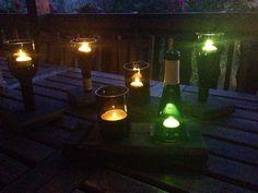 Wine bottle tea lights on wine barrel stave (made by weinARTig)