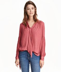 Raspberry. V-neck blouse in soft, textured woven fabric. Tie at neckline, gathers at shoulders, and long, wide sleeves with slit and tie at cuffs. Rounded