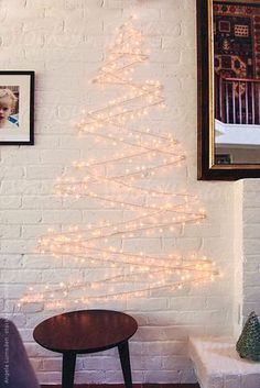 Holiday lights in the shape of a christmas tree on a white brick wall by Angela Lumsden