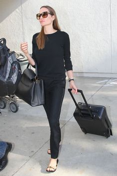 Angelina Jolie wore all black, including a pair of tuxedo pants, while taking off from LAX.