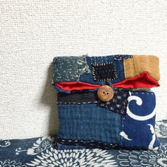 Japanese Boro sashiko pouch, made from vintage Boro kasuri material and is hand-sewn. It closes with a handmade wooden (Japanese ash wood) button. Materials: Kasuri, Aizome, Katazome, Ikat, Indigo, Wood, Cotton, Kilt cotton. Length: 22 cm, ( 8.6 inc ) Width: 16 cm, ( 6.2 inc ) Depth: 4 cm, ( 1.5 inc ) Button: 2.5 cm, ( 0.9 inc )