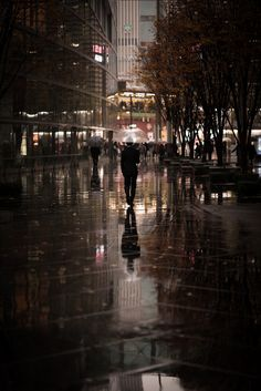 A man walks along in the rain near the Tokyo International Forum in Tokyo, Japan.
