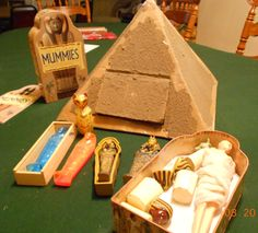 A pyramid you can make out of cardboard, some tape and mix sand/dirt/and glue to cover the sides.                                                                                                                                                      More