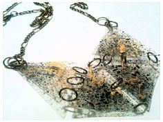 Lekki unikatowy naszyjnik wykonany w jednym egzemplarzu z transparentnej folii PCV o grubości ok. 0,3 mm spryskanej czarną i złotą farbą akrylową.   Całkowita długość naszyjnika to 59 cm.   Doskonale prezentuje się na tle jednokolorowych ubrań.   Długość można regulować.   Elementy metalowe nie zawierają niklu.