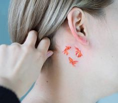 Goldfish tattoos behind the right ear.