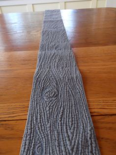A quirky piece, this thin table runner looks like a weathered old piece of wood. It's very unusual and will add a touch of uniqueness to any dining room.  @shannaquilts on etsy.com  100% cotton and machine washable.