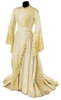 Ivory applique period dress from an unidentified MGM production. (MGM ca. 1950) Ivory long period dress with beautiful self-material leaf applique along front bodice, skirt and bell sleeves. Hook & eye with snap back closure. Studio cleaning tag.