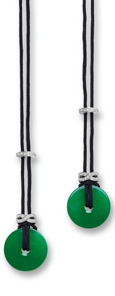 Pair of Jadeite Disc and Diamond Pendant Necklaces The matching pair of jadeite discs of translucent emerald green colour, each accompanied by a black cord with a stylized terminal set with circular-cut diamonds and jadeite beads of matching colour and translucency, mounted in 18 karat white gold, length adjustable.