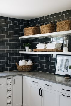 Long white floating shelves are fixed in a black and white laundry room to black subway backsplash tiles over white kitchen cabinets donning oil rubbed bronze pulls and a gray quartzite countertop. White Kitchen, Subway Tile Laundry Room, Kitchen Remodel, White Kitchen Cabinets, Black Subway Tiles, Kitchen, Farmhouse Kitchen Cabinets, Kitchen Tiles, Stools For Kitchen Island