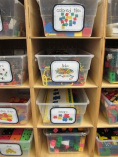 Same-size, clear tubs with large printed labels on shelves store math manipulatives in Adrienne German's kindergarten class.