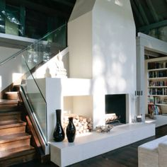 Modern Farmhouse Love - love the glass on the staircase.  love the simple white fireplace and place for wood storage.  modern