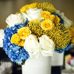 Blue hydrangea, white and yellow roses (sub yellow roses for yellow tulips?), protea in white vase.  Low for conversation.