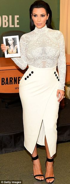 Showing off: The reality star donned a white ensemble consisting of a figure-hugging lace ...