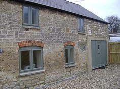 Like the brick detail above grey windows - would also look nice with white render