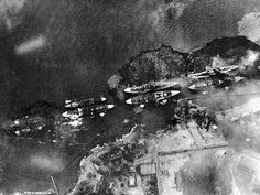 "Vertical aerial view of ""Battleship Row"", beside Ford Island, during the early part of the horizontal bombing attack on the ships moored there. Photographed from a Japanese aircraft.  Ships seen are (from left to right): Arizona with Vestal moored outboard; Tennessee with West Virginia moored outboard; Maryland with Oklahoma moored outboard; and Neosho, only partially visible at the extreme right."