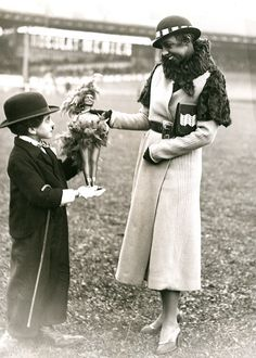"""A Charlie Chaplin imitator offers a Josephine Baker doll to the famous artist at the Fete of the Café Concert at the Velodrome Buffalo cycling track in Paris c. 1930 """""""