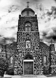 """From our January 1956 issue: """"Beyond Mesilla…is San Miguel, a placita of pink and yellow houses with deep-set windows. … The church of San Miguel is one of New Mexico's most picturesque. It is built of lava rock and perfectly proportioned in its Mission style lines. When more photographers `find' it perhaps San Miguel will rival the Chimayó's Santuario as a photogenic church.""""—Betty Woods (Photo by Mark Jay Goebel, courtesy NewMexi.co)"""