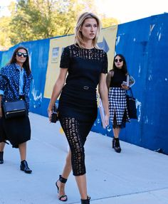 Lauren Remington Platt in a black midi dress + black ankle-strap heels