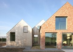 Belgian studio Atelier Tom Vanhee has added two offset gabled volumes onto the side of an existing brick structure near the village of Aartrijke to turn it into a modern home