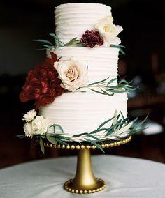 Pretty three-tier wedding cake dressed up with a few flowers and some greenery #weddingcake