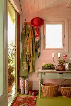 Mudroom entrance to kitchen - spash of bright colour, coat hooks, little table. Love the bright floor.