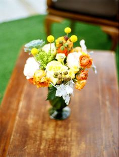Wedding flowers- orange ranunculus and marigold and yellow flowers mixed with berries. wedding by JCG events
