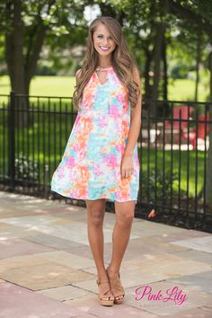 This vibrant tie dye dress is perfect for your next road trip or festival weekend! Featuring neon orange, neon pink, teal, white, purple, and blue, the colors alone are super bright and light! The dress itself is also very airy, with a racerback, no sleeves, and a cute v-shaped cut out detail and metallic button in the front