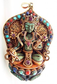 Tibet | Pendant representing Bhodisatva Guanyin or Avalokiteshvara, God of compassion | ca. mid 20th century | Fire gilded silver, turquoise, coral, lapis lazuli and ruby | Price on request