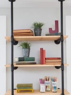 Copy This Look: For a simpler take on the library shelving, create a single bookcase using plumbing pipes and basic lumber.