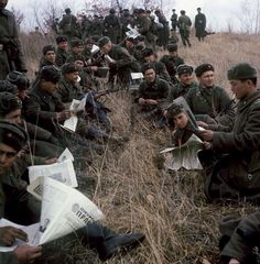 Soviet soldiers taking a break to read the Pravda (the truth) newspaper