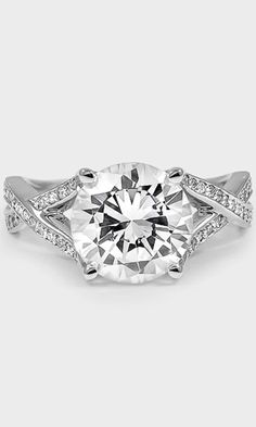 A 3 carat round diamond sparkles at the center of this gorgeous engagement ring.