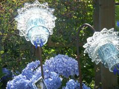 Amazing glass flowers made out of glassware (cups, pitchers, plates, bowls) and displayed on rebar <3