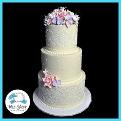 wedding cake featuring sugar flowers and lace stenciling