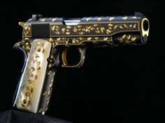 Stunning 9 mm handgun (a Colt 1911, perhaps?), anodized black with pearl grip, engraved gold leafing throughout. I love this so much I'd marry it.