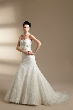 Strapless sweetheart neckline with v back neckline. Lace throughout dress with flower detail on bodice. Asymmetric waistline on flare skirt. Ruffle and lace detail at hemline.
