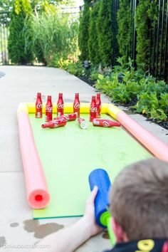 DIY Outdoor Bowling Game, made using Coke bottles, a yoga mat and pool noodles!! Play it with a supersoaker for summer water fun for kids! #outdoorgames